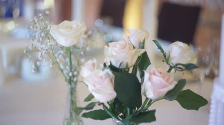 ortanca : Beautiful bouquet of white roses on the wedding table in a restaurant Stok Video