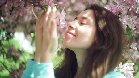 cheirando : Beautiful woman sniffing flowers in the spring garden