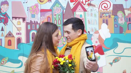 loving young couple doing selfie on wall background