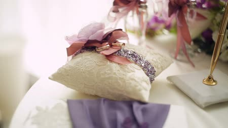 предъявитель : golden wedding rings on small white cushion
