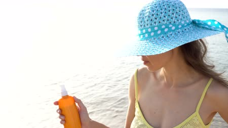 koruma : Sunscreen woman applying suntan lotion on shoulders during summer travel vacation. Beautiful happy woman with solar oil cream in plastic spray bottle on beach