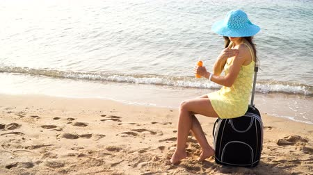 sunblock : Beautiful woman in a hat with a jar of suntan cream in her hands sits on a suitcase against the sea and smears her shoulder during summer travel vacation. Beautiful happy woman with solar oil cream in plastic spray bottle on beach
