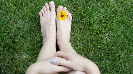 mezítláb : Feet of woman on grass with yellow flower on meadow. HD video motion Stock mozgókép