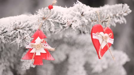 şamdan : red Wooden Christmas toys heart and fir-tree hanging on the branches of the snowly Christmas tree. video motion hd Stok Video