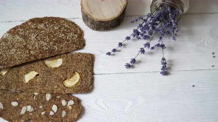 gözenekli : Bread with flaxseeds and almonds on a white wooden background. Useful dietary raw bread vegan breakfast without yeast