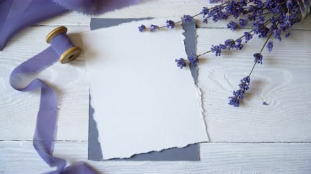 calligraphic : White blank card, envelope and ribbon on a background of pink and blue fabric with lavender flowers on a white background. Mockup with envelope and blank card. Flat lay. Top view Stock Footage