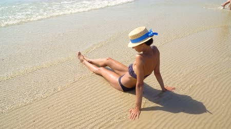 Summer lifestyle HD video of pretty young suntanned woman in a hat. Enjoying life and sitting on the beach, time to travel. Looking at the sea