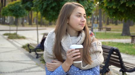 Close-up of the face of woman who drinks hot tea or coffee in autumn park, she wears knitted scarf. girl drinks coffee for good mood from mug Stok Video