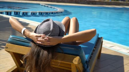 edebi : Pretty woman relaxing in a lounger near of the swimming pool. Consept of the travel vocation