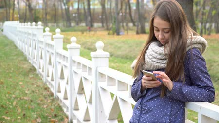 Caucasian woman with knitten scarf using smart phone, typing something during walking in autumn park. video 4k Stok Video