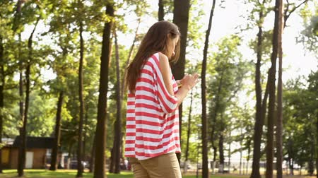 macierzyństwo : Beautiful girl is walking in city park and using smartphone, young woman is holding device and touching screen, summer nature is visible Wideo