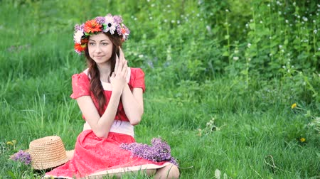 Beautiful woman with wreath picks flowers on meadow. Happy woman in spring or summer season. I love to work with plants Stok Video