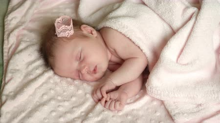 Newborn little baby girl is sleeping on the bed, sweet dreams of little baby, healthy sleep.