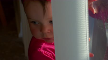 rolety : Adorable little girl plays with blinds at window, 4K Wideo