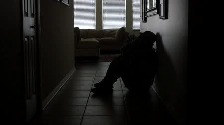 traumatic : A soldiers sits in a dark hallway while dealing with PTSD, WIDE, 4K Stock Footage