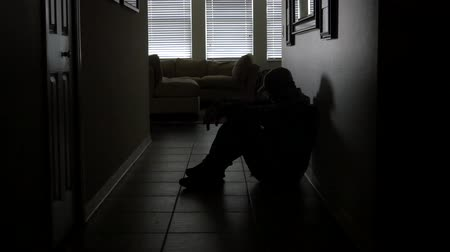 veterano : A soldiers sits in a dark hallway while dealing with PTSD, WIDE, 4K Stock Footage