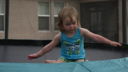 küçük kız : Cute little girl plays on her trampoline, 4K