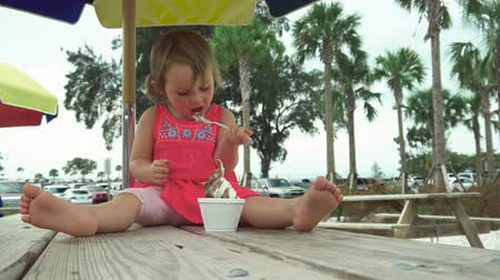 çikolata : Cute little girl with pig tails eating ice cream on a picnic table Stok Video