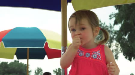piknik : Cute little girl with pig tails eating ice cream on a picnic table Stok Video