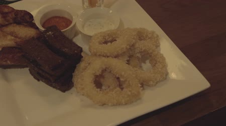 паб : Squid rings, fried wings, toast on a plate with sauce. Snack to beer Стоковые видеозаписи