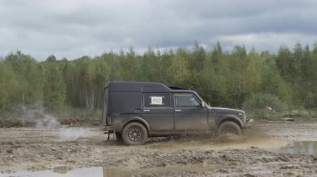 néző : Jeep rides on a dirt road. The car enters the puddle of mud