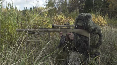 стрельба : Sniper rifle in protective suit sitting in a field Стоковые видеозаписи