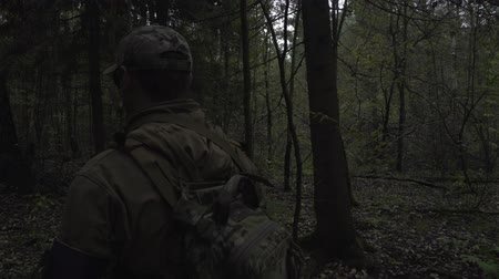 harcerz : Soldier with a gun in his hand goes through the dark forest