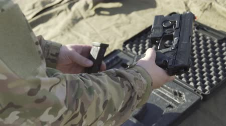 пистолеты : The soldier pulls a gun out of the case and insert the pistol with ammunition clip Стоковые видеозаписи