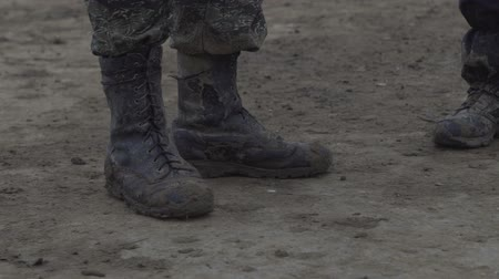 boggy : People stand in muddy boots. Dirty shoes and clothes