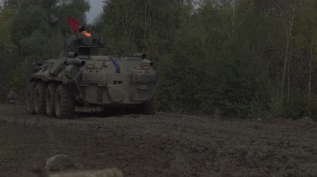 armature : Military armored personnel carrier travels along the muddy road. Dirty armored vehicle