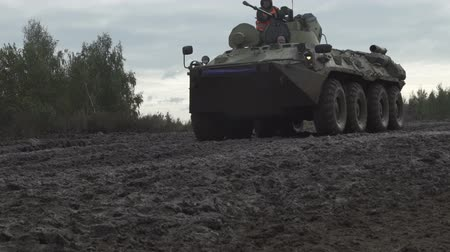 бронированный : Military armored personnel carrier travels along the muddy road. Dirty armored vehicle
