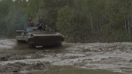 armoured : Military armored personnel carrier travels along the muddy road. Dirty armored vehicle