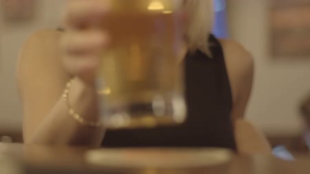 duygusallık : young blond woman drinking a glass of beer at a bar