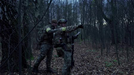 invisible : war in the woods with a gun looking at the map