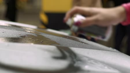 repaint : girl gets a paint from a container on a white car body