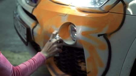 tuning : girl gets a paint from a container on a white car body