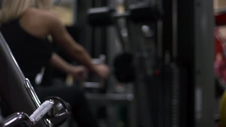 biceps curls : Blonde girl training at the gym. Woman engaged in fitness
