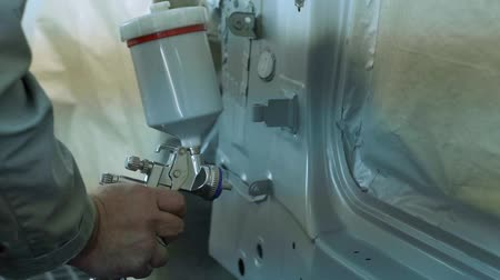 fender : master paints the body of the spray gun in a car workshop