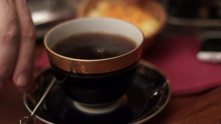sweetener : Black cup with tea and sugar