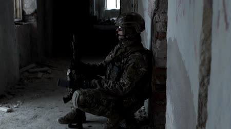 defending : A military man with a weapon is ambushed in an abandoned building Stock Footage