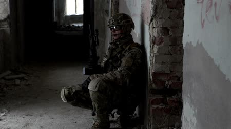 винтовка : A military man with a weapon is ambushed in an abandoned building Стоковые видеозаписи