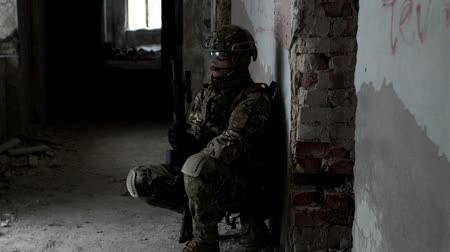 special police : A military man with a weapon is ambushed in an abandoned building Stock Footage