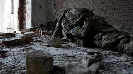 defending : Military man with arms lies in ambush in an abandoned building Stock Footage