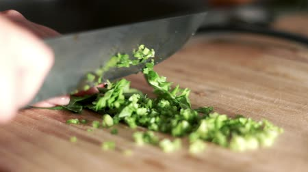 abilities : Woman is cutting parsley knife on wooden board. Cooking food. Food Ingredients Stock Footage