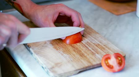 klín : Man cuts tomato with knife on wooden board. Preparation salad with tomatoes