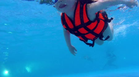 preserver : Child swimming under water slow motion. Children in life jacket swims underwater
