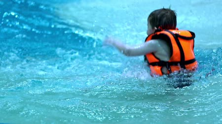 preserver : Children playing in water swimming pool slow motion. Child in swimming pool