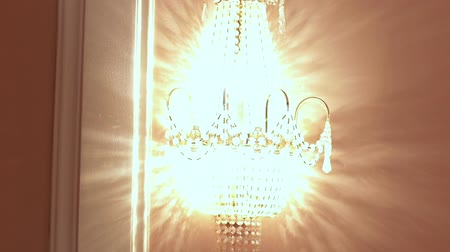 šperk : Glowing crystal sconce hanging on wall. Crystal chandelier