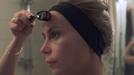 mezoterapia : Young woman using a derma roller for micro needling therapy face.