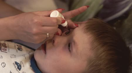 alergie : Mother drips her son in eye medical solution. Healthy care concept Wideo